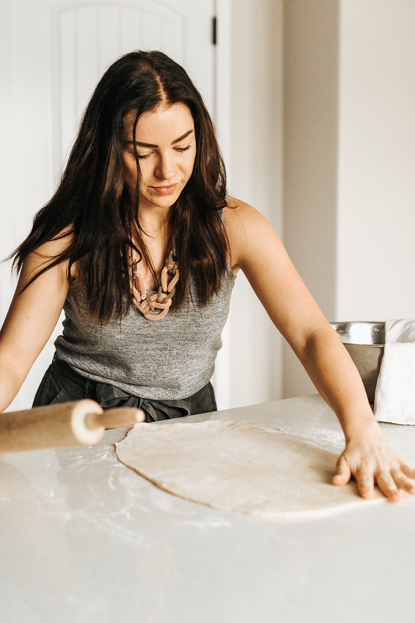 Me, a brunette woman rolling dough for cannoli rolls.